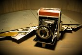 Retro Old Vintage Outdated Manual Film Camera Circa 1940s And Vintage Photo Album On Wooden Table. V poster