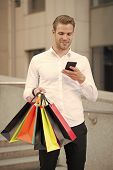 Businessman Use Shopping Application. Man Carries Shopping Bags While Hold Phone Urban Background. S poster