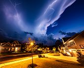 Powerful lightning storm front passes over residential houses poster