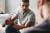 Photo of brooding unshaven man having conversation with psychologist on therapy session in room poster