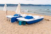 Two Pedal Boats Standing On The Shore, Both Folded Umbrellas In Sunny Beach, Bulgaria. In The Backgr poster