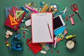 Red clipboard with blank sheet, computer tablet, microscope and stationery accessories  on green bac poster