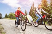 Family With Child In Trailer Riding Mountain Bikes In Alps poster