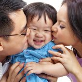stock photo of little young child children girl toddler  - Parents giving their daughter a kiss - JPG