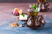 Traditional Turkish Tea With Mint Leaves And Sweets In A Traditional Glass On A Concrete Background poster
