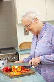 Senior woman chopping vegetables in domestic kitchen poster