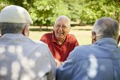 stock photo of mating  - Active retired senior people old friends and leisure group of three elderly men having fun laughing and talking in city park - JPG