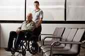 Постер, плакат: Портрет молодого человека с его дед на инвалидной коляске в вестибюле больницы