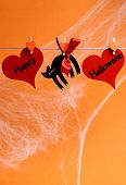 picture of home is where your heart is  - Happy Halloween message written across red hearts and black cat with pegs hanging from a line against an orange background - JPG