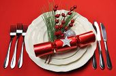 foto of posh  - Modern bright red Christmas table setting with cracker and baubles plates and cutlery on a red tablecloth background - JPG
