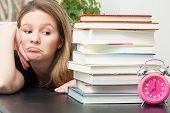 pic of time study  - A young woman glances sideways at the large pile of books for exam study time - JPG