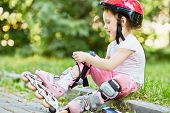 Little girl in protective equipment and rollers sits on curb of walkway in park, fastening knee-pad