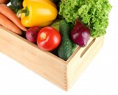Fresh vegetables in wooden box on grey background