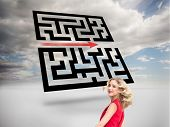 Composite image of smiling blonde in red dress twirling in front of holographic maze in sky