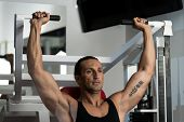 foto of rep  - Fit man doing shoulder presses on a weight machine at the health club - JPG