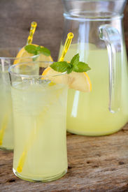 picture of mint leaf  - Two glasses of fresh lemonade garnished with lemon slices and mint leaves. Used a wood textured background for a rustic look.