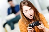 picture of controller  - Portrait of beautiful woman playing videogame at home - JPG