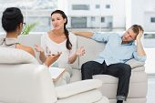 image of therapist  - Angry couple sitting on couch talking to therapist in therapists office - JPG