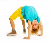 stock photo of upside  - Happy 8 years old boy standing in acrobatic pose upside down on hands - JPG