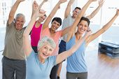 stock photo of studio  - Portrait of smiling people doing power fitness exercise at yoga class in fitness studio - JPG