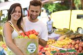picture of papaya  - Couple shopping at open street market carrying a paper bag with a 100 - JPG