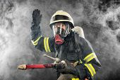 picture of firefighter  - Firefighter giving directions in burning place with smoke - JPG