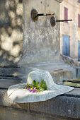 stock photo of peace-pipe  - Sunhat with real flower on a Provencal fountain in Porvence France - JPG