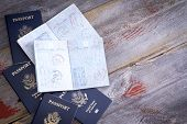 stock photo of passport cover  - American passports lying on a rustic wooden table open to reveal hand stamps from customs officials on border control applied during traveling abroad - JPG