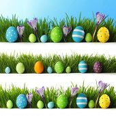 Collection of decorated easter eggs and flowers in grass with copy space