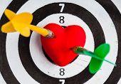 stock photo of bullseye  - Closeup of black and white target with two dart in red valentine heart love symbol as bullseye - JPG