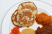 foto of ling  - Pancakes on a white plate with different red caviar - JPG