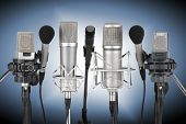 stock photo of microphone  - Studio shot of seven professional microphones in a row on blue background with spotlight - JPG