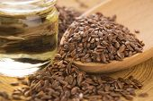 stock photo of flax seed  - Linseed oil and flax seeds on wooden background - JPG