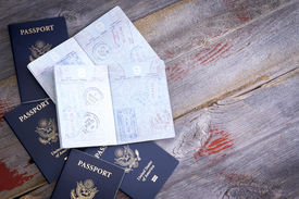 foto of passport cover  - American passports lying on a rustic wooden table open to reveal hand stamps from customs officials on border control applied during traveling abroad - JPG