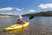 foto of kayak  - Woman Kayaking on Beautiful Peaceful Mountain Lake - JPG