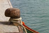 image of bollard  - Rusty bollard with rope on the pier - JPG