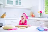 pic of little young child children girl toddler  - Adorable little child funny curly toddler girl in a pink chef hat baking a pie rolling dough sitting in a white sunny kitchen with big window - JPG