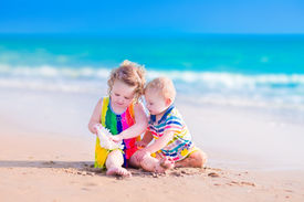 picture of little sister  - Happy baby boy and little curly toddler girl brother and sister playing with a huge sea shell in sand on a beautiful exotic tropical beach with turquoise water having fun on vacation - JPG