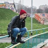 image of anarchists  - Punk guy with beanie posing in a city park - JPG