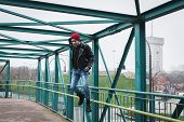 picture of anarchists  - Punk guy with beanie jumping on a bridge - JPG