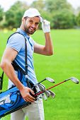 pic of ball cap  - Rear view of young happy golfer carrying golf bag with drivers and looking over shoulder while standing on golf course - JPG