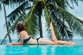 stock photo of infinity pool  - A sexy young woman is relaxing by a swimming pool with palm trees and the ocean in the background - JPG