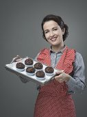 image of apron  - Smiling vintage woman in apron serving homemade chocolate muffins on a tray - JPG