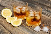 stock photo of scotch  - Glass with Scotch and ice on old wooden background - JPG