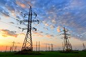 image of power transmission lines  - Electric power lines against sky at sunrise - JPG