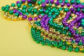 stock photo of beads  - Colorful Mardi Gras beads on yellow background with copy space - JPG