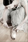 picture of ankle shoes  - Ballerina tying her old worned pointe shoes before her rehearsal - JPG