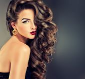 picture of brunette hair  - Beautiful model brunette with long curled hair and fashion makeup - JPG