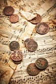 stock photo of copper coins  - Old coins on vintage music notes background - JPG