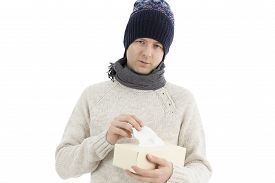 picture of tissue box  - Adult caucasian man is having cold taking tissue from tissue box - JPG